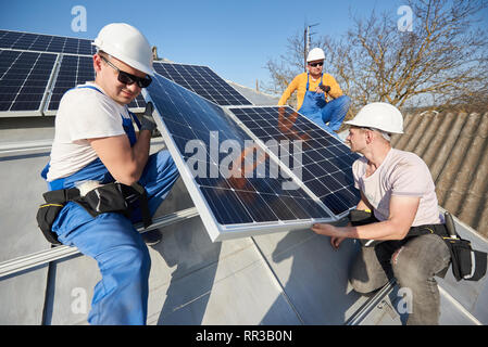 Male workers installing solar photovoltaic panel system. Electricians lifting blue solar module on roof of modern house. Alternative energy ecological concept.