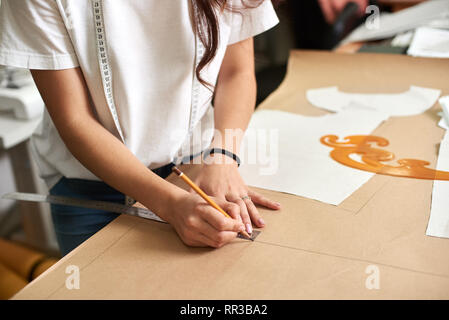 Workplace in design studio, pattern creation process. Female designer hands close-up making drawing lines on cardboard using pencil and ruler. Exclusive clothes making, creative occupation concept. - Stock Photo