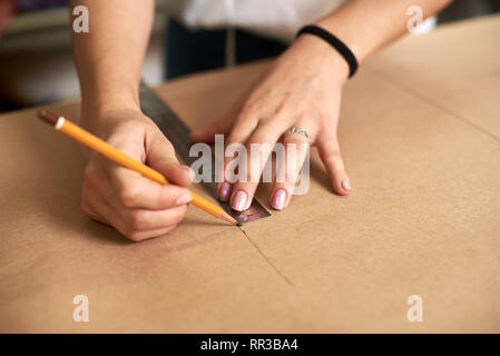 Work place in design studio. Professional female designer hands close-up making paper patterns using measuring tape, ruler and curves. Exclusive clothes making, creative occupation concept. - Stock Photo