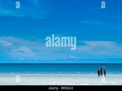 People walking on beach with wide view of sea and blue sky - Stock Photo