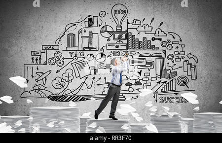 Businessman playing fife while standing on pile of documents among flying paper planes with business-plan information on background. Mixed media. - Stock Photo