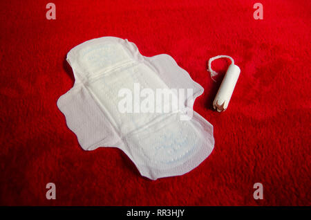 Sanitary pad and tampon on red blanket pms concept - Stock Photo