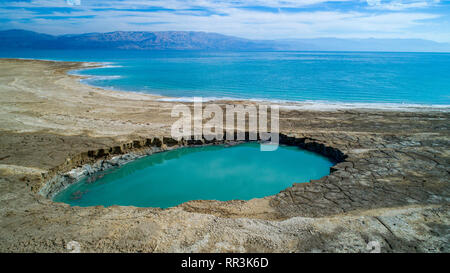 Aerial Photography with a drone. Elevated view of sink holes on the shore of the Dead Sea, Israel. The sink holes are caused by the rapidly receding w - Stock Photo