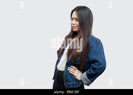 Spin or kidney pain. Profile side view portrait of beautiful brunette asian young woman in casual blue denim jacket standing and touching her back. st - Stock Photo