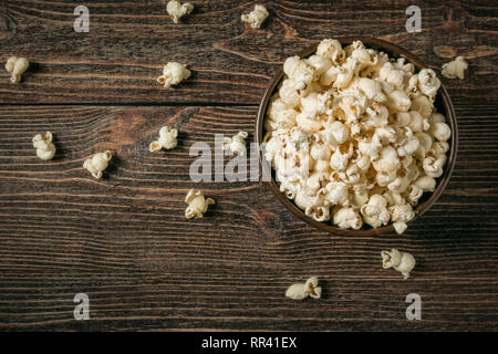 Popcorn in bowl on old wooden background. Copy space. - Stock Photo