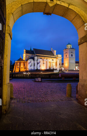View to St. Anne's Church at night from arched gate of the Royal Castle in city of Warsaw in Poland - Stock Photo