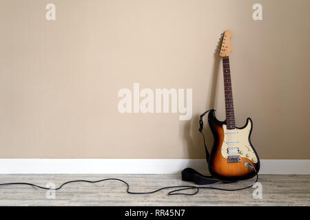 Electro guitar with cable on wall background. Music instrument concept - Stock Photo