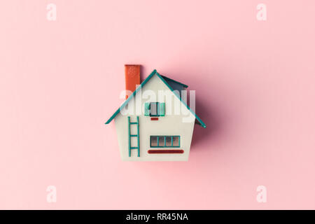 Plastic house model on pink background. Real estate concept - Stock Photo