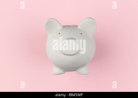 White piggy moneybox on pink background. Financial concept - Stock Photo