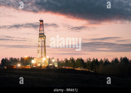 Oil gas drilling rig on sunset background. Industrial concept - Stock Photo