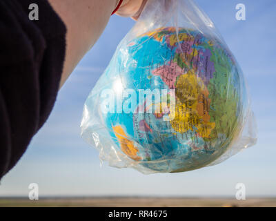 A person with a terrestrial globe or planet Earth in his hands inside a plastic bag. Ecology concept - Stock Photo
