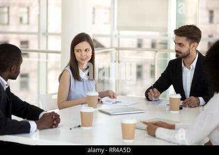 Diverse business team discussing sitting together at meeting - Stock Photo