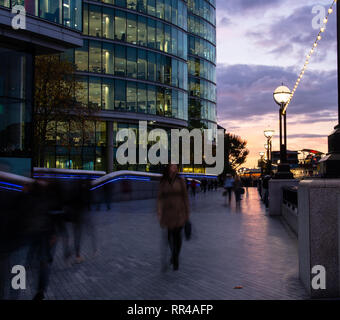 London, United Kingdom - October 18 2018:   Pedestrians walking along the Southbank of London at sunset - Stock Photo