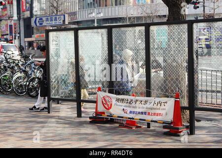 A designated smoking area in Tokyo's Shinjuku area. - Stock Photo
