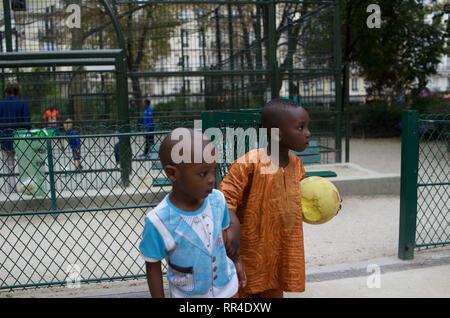 French children of African origin, one boy wearing traditional dashiki shirt, holding yellow sponge ball, Square de Maubeuge, 75009, Paris, France - Stock Photo