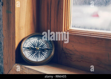 Compass on wooden window for travel and navigation concept - Stock Photo