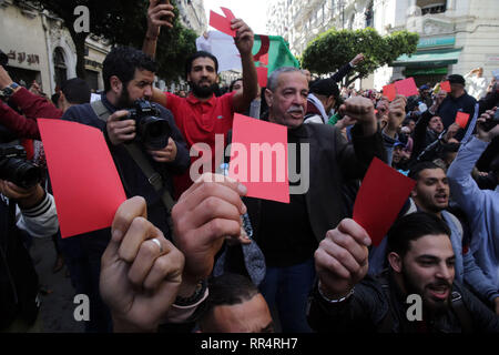 Algiers, Algeria. 24th Feb, 2019. Algerian protesters hold up red cards during a demonstration against the candidacy of Algerian President Abdelaziz Bouteflika for a fifth term in office. Bouteflika, who has been the President of Algeria since 1999, will run again for office during the 2019 Algerian Presidential Election, which to take place on 18 April 2019. Credit: Farouk Batiche/dpa/Alamy Live News - Stock Photo