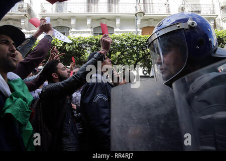 Algiers, Algeria. 24th Feb, 2019. Algerian protesters hold up red cards in front of policemen during a demonstration against the candidacy of Algerian President Abdelaziz Bouteflika for a fifth term in office. Bouteflika, who has been the President of Algeria since 1999, will run again for office during the 2019 Algerian Presidential Election, which to take place on 18 April 2019. Credit: Farouk Batiche/dpa/Alamy Live News - Stock Photo
