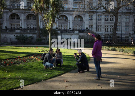 London, UK. 24th February, 2019. Londoner takes a picture of two tourists together with his dog in Whitehall Gardens, Westminster, early afternoon on this sunny, February spring like day. Credit: Joe Kuis /Alamy Live News - Stock Photo