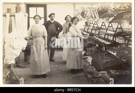 Early 1900's postcard of bobbin winder girls and foreman, overseer or workman. Dried skeins of cotton from the rack are put on the swift of the winding machine that winds yarn from the skein onto bobbins, Circa 1915, Lancashire, U.K. - Stock Photo