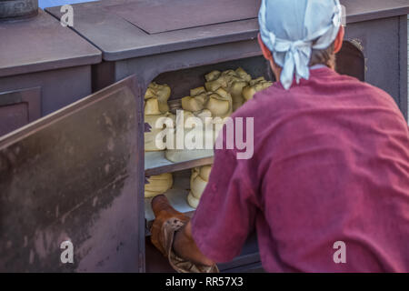 Traditional metal oven view with baker removing the already cooked bread... - Stock Photo
