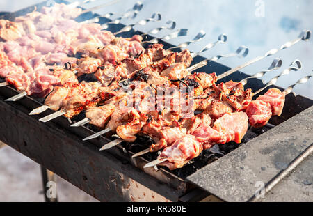 Grilled appetizing kebab cooking on metal skewers. Shashlik made of cubes of meat during of cooking on the mangal over hot charcoals outdoors, street  - Stock Photo