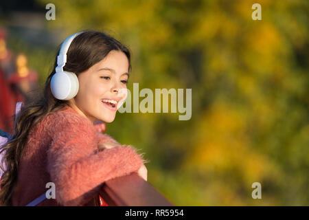 Get happy yourself. Girl modern headphones enjoy relax. Look on bright side. Secrets to raising happy child. Girl cute kid green grass background. Healthy emotional happy kid relaxing outdoors. - Stock Photo
