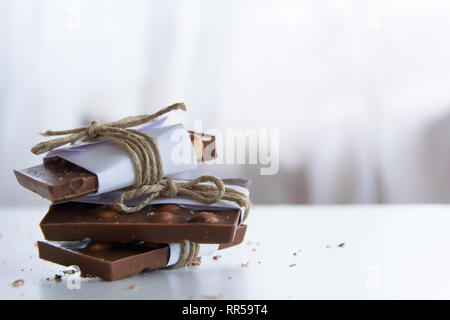 Front view of broken chocolate pieces wrapped in white paper and rustic twine on the white background - Stock Photo