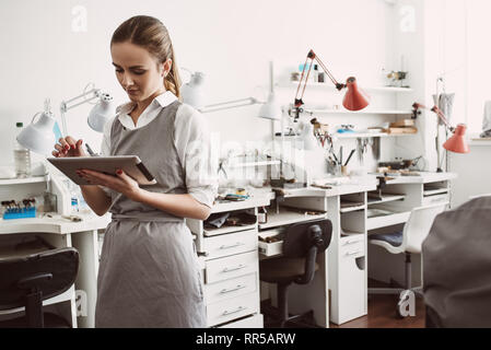Online production. Close up portrait of young female jeweler in apron using CRM system on her digital tablet while standing at her jewelry workshop. B - Stock Photo