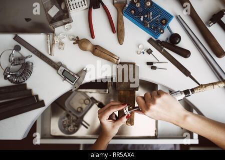 Creative chaos. Top view of jeweler's workbench with different tools for making jewelry. Female jeweler's hands polishing a silver ring with grinding  - Stock Photo