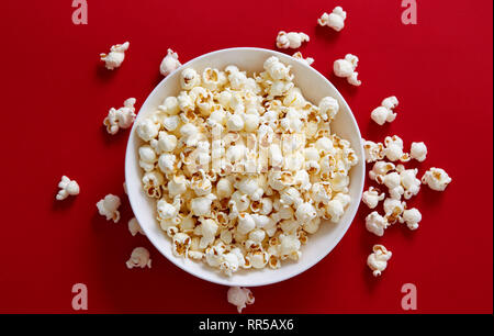 Popcorn in a white bowl. Directly above shot of popcorn against red background.