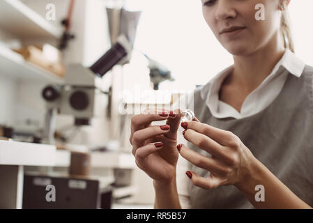 No limit to perfection. Close up of female jeweler examining the silver ring at workshop. Woman goldsmith inspecting jewelry. - Stock Photo