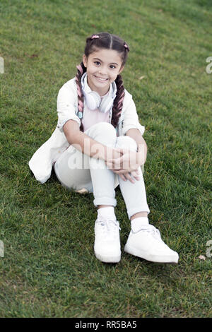 Secrets to raising happy child. Girl cute kid green grass background. Healthy emotional happy kid relaxing outdoors. Get happy yourself. Girl braids hairstyle and modern headphones enjoy relax. - Stock Photo