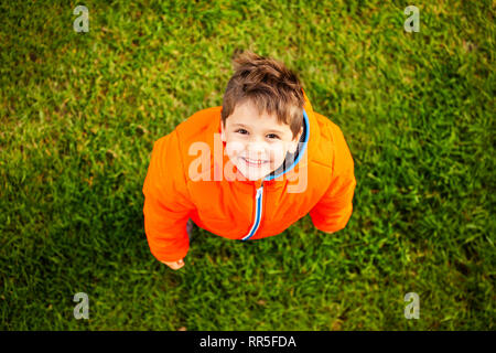 Top view of smiling boy standing on green grass - Stock Photo