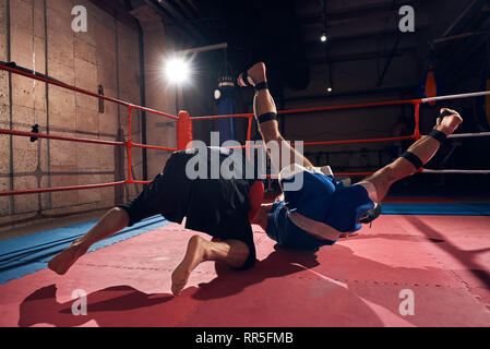 professional fighter practicing mma with his trainer in the ring at the health club - Stock Photo