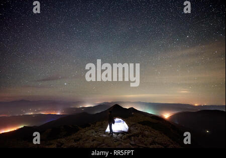 Tourist summer camp at night on the top of the rocky mountain. Silhouette of male hiker resting beside glowing tent under beautiful night sky full of stars. On background starry sky and luminous towns - Stock Photo