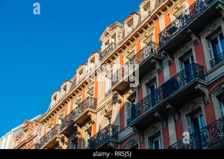 Majestic balconies view from below of French Haussmannian apartment building with clear blue sky early in the morning - real estate property management luxury in France - Stock Photo