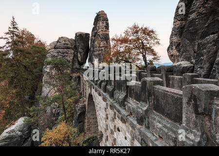 Side view of the Bastei bridge in the Saxon Switzerland National Park from the Elbe Sandstone Mountains. Rock formations and trees in autumn. visible - Stock Photo