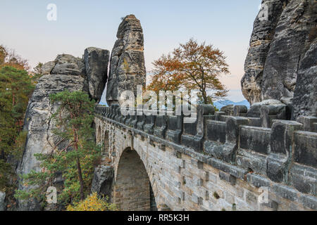 Side view of Bastei bridge with a view of the rock gate. Trees and rock formation from Elbe Sandstone Mountains in the Saxon Switzerland National Park - Stock Photo
