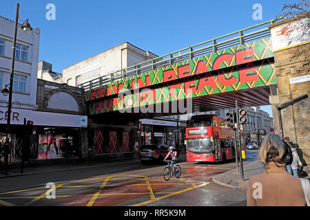 Stay in Peace sign on railway bridge over Brixton Road and people, traffic  in street in Brixton, South London SW9 England UK  KATHY DEWITT - Stock Photo