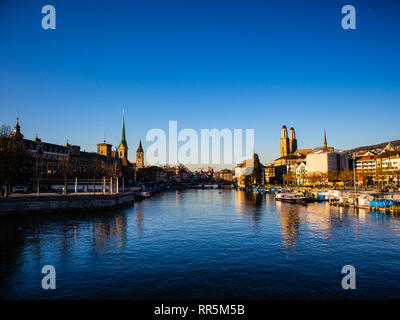 View of historic Zurich city with famous Fraumunster and Grossmunster Churches and river Limmat at Lake Zurich on a sunset in winter, Switzerland - Stock Photo