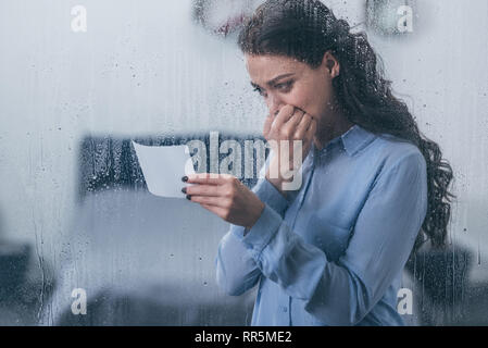 grieving woman holding photograph, covering mouth with hand and crying at home through window with raindrops - Stock Photo