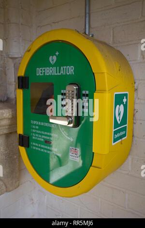 Public access defibrillator with emergency keypad lock on wall - Stock Photo