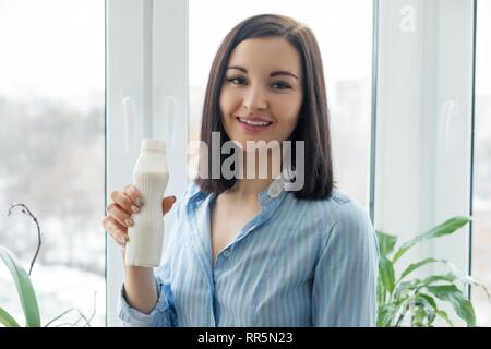 Morning portrait of young smiling woman drinking milk drink yogurt from bottle, woman standing at home in shirt near the window, healthy food eating. - Stock Photo