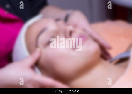 Blurred scene of masseuse massages beautiful young woman's face with hands in the salon. - Stock Photo