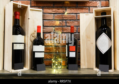 Four bottles of wine with empty labels in wooden boxes on brick wall background. - Stock Photo