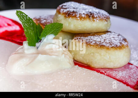 Traditional Russian sweet fried cheese cakes elegantly served on a plate with sour cream and jam, sprinkled with sugar in Russia - Stock Photo
