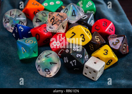 various polyhedral game dice strewn about on a table - Stock Photo