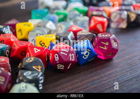 various plastic polyhedral game dice strewn about on a wooden table - Stock Photo