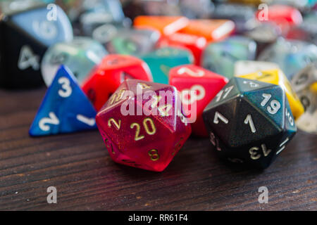 various colorful polyhedral game dice on a table with a 20 and a one in the foreground - Stock Photo